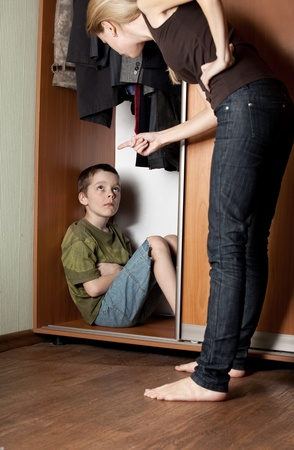 argues: Mother scolding her son at home, in a closet. Stock Photo