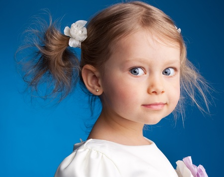 little girl smiling: Beautiful little girl on a blue background Stock Photo