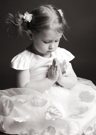 REZANDO: Orar niña sobre fondo gris Foto de archivo
