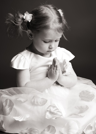 Praying little girl on gray background photo