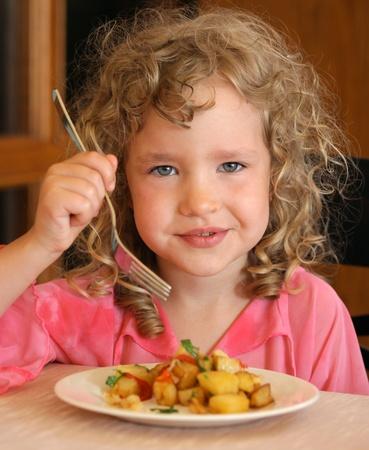 ni�os comiendo: Ni�a comiendo patatas Foto de archivo