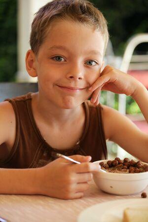 niños desayunando: Niño feliz comiendo granola Foto de archivo