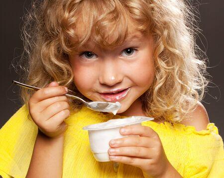 little girl eating: Little happy child eating yogurt