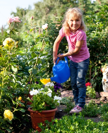 watering can: Child watered from watering the flowers in the garden