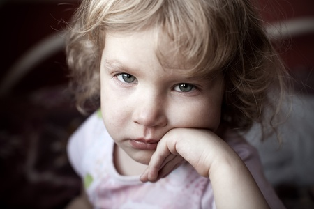 Sad little child looking at camera