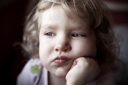 lament: Sad little child looking away