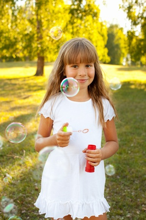 Happy child with bubbles outdoors photo