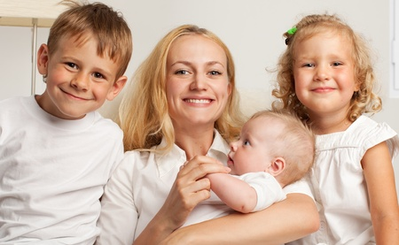 Mother with three children at home photo