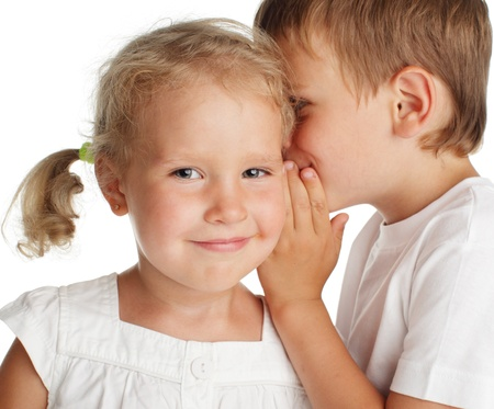 Boy whispers a secret to the girl photo