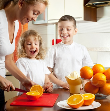 Happy mother with children squeezed orange juice photo