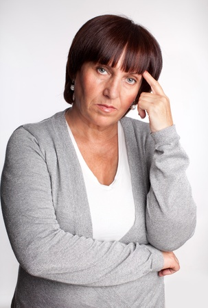 mature women only: Sadness mature woman. Isolated on gray Stock Photo