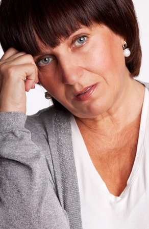 depressed woman: Sadness mature woman. Isolated on gray Stock Photo