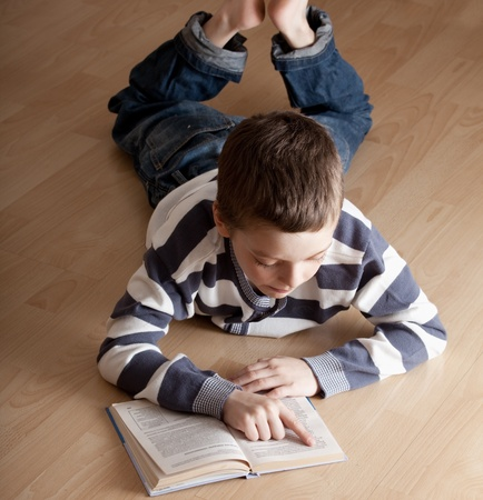 Child reeding book lying on the floor photo
