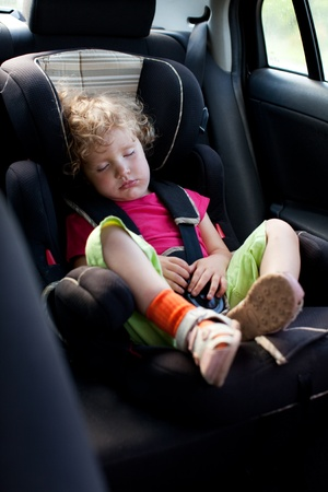 Sleeping child in an automobile armchair photo