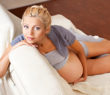 pregnant relaxing on sofa: Beautiful young pregnant woman at home Stock Photo