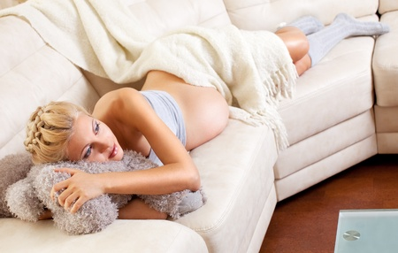 lying on the stomach: Beautiful young pregnant woman at home Stock Photo