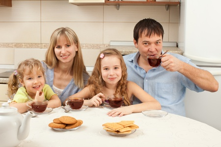 Happy family at breakfast in the kitchen photo