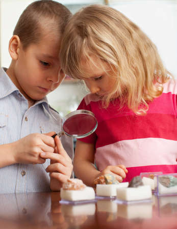 Children are considering a magnifying glass collection of stones photo