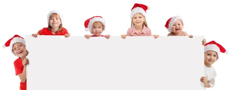 child holding sign: Happy kids  in christmas caps, holding the banner in his hand