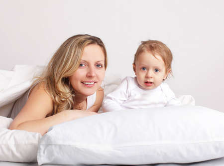 Mother with baby on bed photo