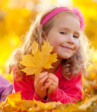 Happy little child in autumn park photo