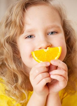 frutas divertidas: Ni�o con naranja. Ni�a feliz con fruta en casa.