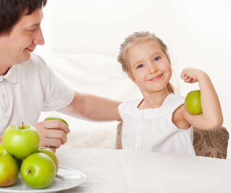 Padre e hijo comiendo manzanas. Familia en su casa en la cocina Foto de archivo - 12940303