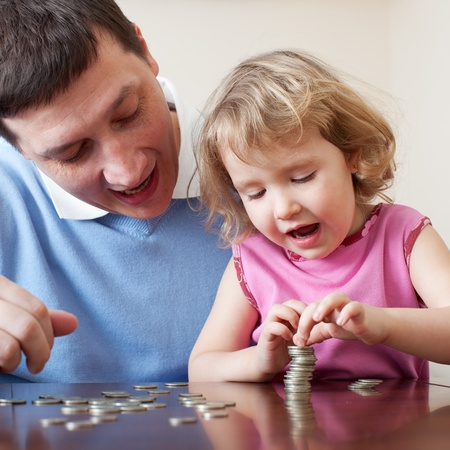 teaches: Father and daughter puts coins. Father teaches the child Finance