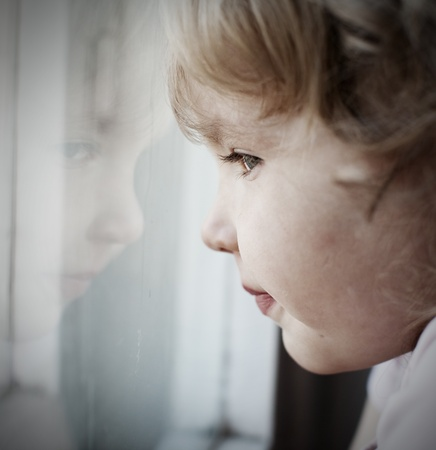 children sad: Sad little girl looking at window