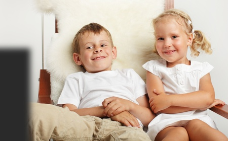 Brother and sister watching TV at home photo