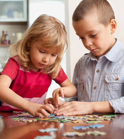 two persons only: Children, playing puzzles at home Stock Photo
