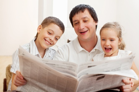 magazine reading: Happy family reading a newspaper. Father with daughter and son Stock Photo