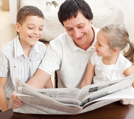 Happy family reading a newspaper. Father with daughter and son Stock Photo