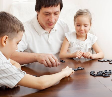 dominoes: Family that plays dominoes. Father playing with children at home