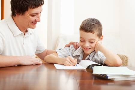 two parents: Father helping son do homework. Parent helps his child Stock Photo