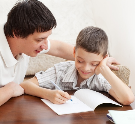 helping children: Father helping son do homework. Parent helps his child Stock Photo