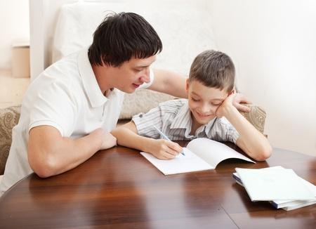 padres e hijos felices: Padre e hijo ayuda a hacer la tarea. Los padres ayuda a su hijo
