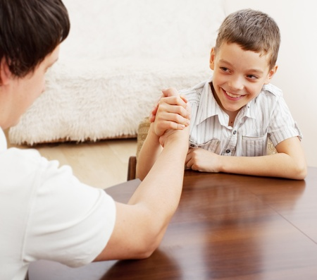 boy muscles: Father and son arm wrestling. Dad play with child