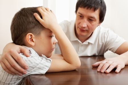 adversity: Father comforts a sad child. Problems in the family
