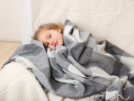 Illness child. Little girl wrapped in a blanket photo
