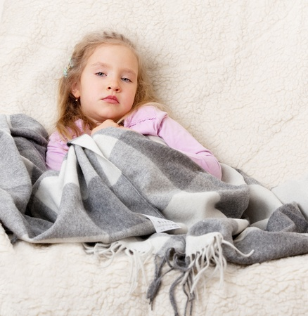 La enfermedad infantil. Ni�a envuelto en una manta Foto de archivo - 12940313
