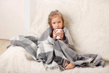 bambini tristi: Malattie dei bambini. Bambina avvolta in una coperta con la tazza