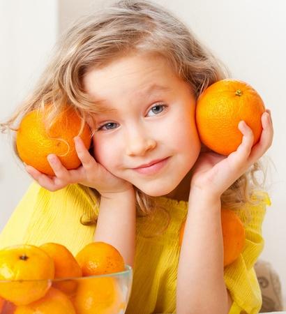 naranjas: Niño con naranja. Niña feliz con fruta en casa.