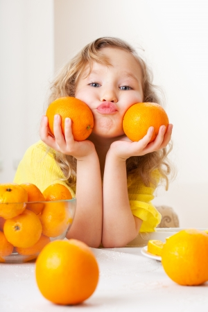 ni�os comiendo: Ni�o con naranja. Ni�a feliz con fruta en casa.