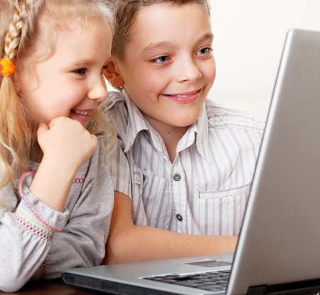 computer learning: Children with laptop indoors. Happy kids playing computer at home. Stock Photo