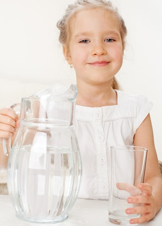 Child with glass pitcher water. Little girl drinking water at home Stock Photo - 13083219