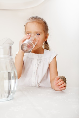 replenishment: Child with glass pitcher water. Little girl drinking water at home