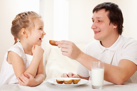 Child with father have a breakfast. Family eating at home photo