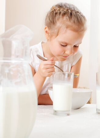 Child eat breakfast. Girl eating cereals with milk photo
