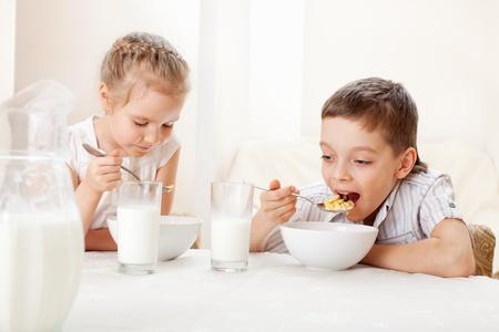 niños comiendo: Los niños comen desayuno. Familia comiendo cereales con leche
